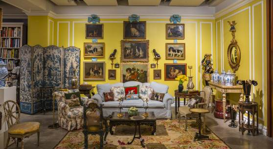 """Mario Buatta's Manhattan apartment photographed for Architectural Digest in 1997. The living room is glazed in three shades of lime green and creamy white, with a faux-sisal painted floor. Over the sofa hangs Mario's collection of dog paintings. Mario often joked, """"These paintings are my ancestors. Seriously, I love dogs. I don't have a dog because I have such a busy schedule, but I love viewing them on the wall."""" Photo: Scott Frances for Architectural Digest/Otto Archive Bildquelle: Sotheby's A"""