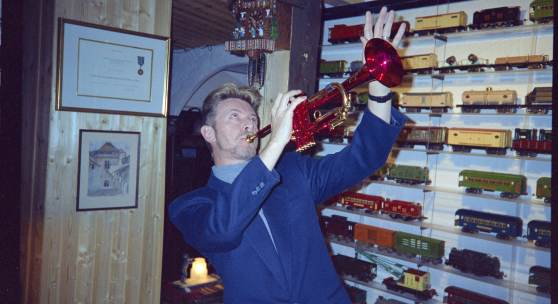 David Bowie mit der Trompete von Miles Davis vor Modelleisenbahnen im Chalet «Le Picotin», 1995, Caux (VD). © Claude Nobs Archives