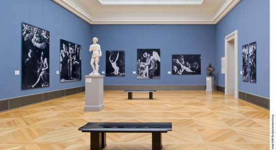 Bode-Museum, Blick in Saal 257. Fotoabzüge in Originalgröße von Gemälden von Guido Reni, Francisco de Zurbarán, Jusepe de Ribera, Caravaggio und Petrus Christus; in der Mitte steht der Abguss des Johannes des Täufers, den Bode für ein Frühwerk Michelangelos hielt (wahrscheinlicher Rom, um 1600); rechts steht der Abguss der bronzen Büste des Francesco del Nero von Giulio Mazzoni, um 1560 - alle Werke seit 1945 verschollen. © Staatliche Museen zu Berlin, Skulpturensammlung und Museum für Byzantini