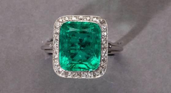 Außergewöhnlicher Smaragd-/Diamantring. Hochfeiner Smaragd im Tafelschliff, ca. 6 ct. Entouriert mit ca. 0,28 ct. Diamanten. Fassung vermutlich Platin