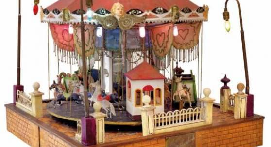 Nr. 201 Karussell, gebaut von August Schönenbeck, vermutl. für elektrischen Betrieb, Pferde, Wagen und zwei Häuschen, dekoriert mit seidenen Perlen geschmückten Fahnen, Glühlampen, Breite 66 cm, H. 60 cm Rufpreis € 1.200
