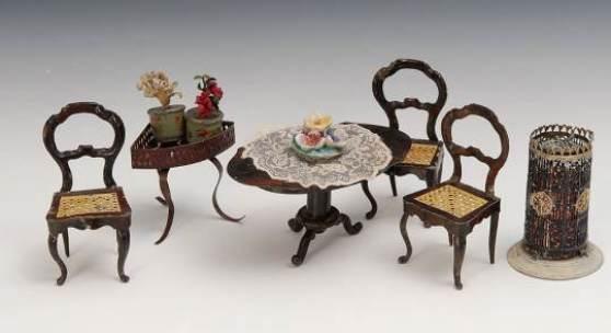 4 Blechmöbel Rock & Graner + Blumentisch und Zinnofen. Ovaler Tisch und 3 Stühle mit Ballonlehne und gestanzter Sitzfläche in Geflechtoptik. H 9,5 cm. Dazu seltener lackierter Zinnofen und Eck-Blumentisch aus Blech. Bespielt mit Altersspuren. ABB.B 9