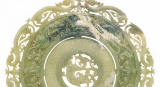 1226 Außergewöhnliche Bi-Scheibe China 18. Jh. Hellgrüne Jade, geschnitzt. Scheibenförmiger, durchbrochen gearbeiteter Korpus mit feinen Schnitzereien auf beiden Seiten in Gestalt von Drachen und Buddhas. D. 23 cm.
