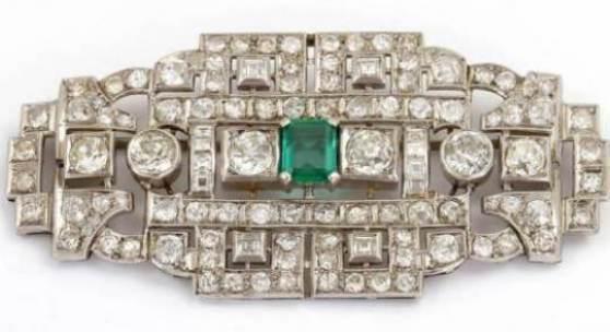 Große Art-Déco Brosche 750/-WG, 1.H.20.Jh. Hochdekorativer Unikatschmuck, m. Diamanten reich verzierte Handarbeit im typischen Art-Déco Durchbruchmuster. Als Mittelstein 1 facettierter, achteckiger Smaragd, ca. 1,2 ct. 114 Dia., u.a. Altschliff u. Carrée, zus. ca. 12,1 ct. tw-tcr-cr if-vsi-p1. LxB: 69 x 34 mm, ca. 22,7 g. Mit Orig. Etui. Zertifikat/Wiederbeschaffungswert v. 1995: ca. DM 65.000,-. Preis & Bieten Schätzpreis: 14.000 €