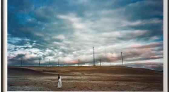 2137 Chen, Jiagang Geb. 1962 Sichuan. «Temptation-25 - Afterlight». Lambda Print. Unter einem spektakulären, weiten Abendhimmel mit dramatischer Wolkenbildung eine karge Wüstenlandschaft mit einigen Strommasten am Horizont. Im Vordergrund eine chinesische Frau mit langem, schwarzem Haar und weißem Kleid verträumt für die Kamera posierend. U.r. chinesisch bez., 3/12 num., sign. und 2008 dat. H. 110, B. 175,5 cm