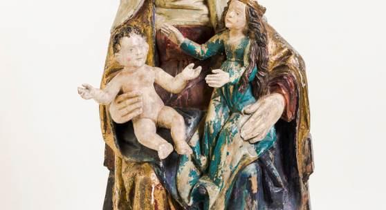 727 Anna Selbdritt, Holz. Dreiviertelrund geschnitzt, verso gehöhlt. Thronende Anna auf ihrem linken Schoß ihre Tochter Maria umfassend, auf der anderen Seite den nackten Jesusknaben haltend. Gold gehöht, ältere farbige Fassung, in Teilen übergangen. (Arme des Jesusknaben rest., Farbabspl.). Um 1700. H. 105 cm. 2.800,00 €