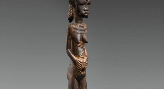 A BAULE FIGURE  Ivory Coast  The standing female with hands on the abdomen, the coiffure with tall top knot and three plaits, keloids on face, neck and body, on circular base, dark glossy patina.  43 cm. high Provenienz  Christie's London, 7 July 1982, lot 19.  Schätzpreis: €15.000 - €20.000, Ergebnis: 40.000