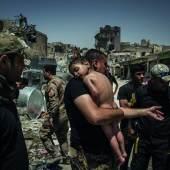 12. Juli 2017 Soldaten der irakischen Spezialeinheiten versorgen einen unidentifizierten Jungen. Er wurde von einem mutmaßlichen IS-Anhänger aus dem letzten vom IS kontrollierten Gebiet der Altstadt von Mossul, Irak, herausgetragen. Da der Mann den Namen des Jungen nicht kannte, gingen die Soldaten davon aus, dass er ihn bei seinem Fluchtversuch als menschliches Schutzschild benutzte. Ivor Prickett for The New York Times
