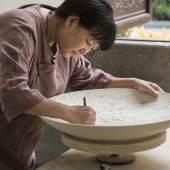 Meisterin Yang Jianqin bei der Anfertigung eines feinen Schnitz- und Ritzdekors. Foto: Franca Wohlt, 2018