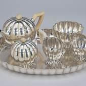 Nr. 103 Josef Hoffmann, großes sechsteiliges Teeservice, Wiener Werkstätte, um 1919, Silber, zum Teil mit Hammerschlagdekor; Henkel und Deckelknäufe aus geschnitztem Elfenbein; bestehend aus: großem ovalen Tablett (H. 4,2 cm, L. 44,4 cm, B. 36,3 cm); Teekanne mit Scharnierdeckel (H. 16,4 cm); Oberkanne (H. 10,3 cm); Zuckerdose mit Deckel (H. 13,4 cm); größere Schale (H. 9,7 cm) und kleinere Schale (H. 7,6 cm); Gebrauchsspuren Schätzwert € 25.000 – 40.00