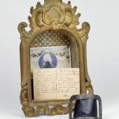 Wolfgang Amadeus Mozart (1756 – 1791) Persönliche Schuhschnalle, Messing mit Silberauflage, floral ornamental graviert, eiserner Dorn,8,5 x 7,2 cm, mit handschriftlicher Dokumentation in verglastem Schaukasten, Schätzwert € 2.000 – 4.000 Auktion 30. Oktober 2017