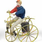 Nr. 104 Radfahrer, männliche Puppe mit Porzellankopf und anmodellierter Kappe auf einem dreirädrigen Fahrrad, H. 25,5 cm Rufpreis € 1.500