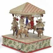 Nr. 200 Ringelspiel mit Pferdchen und Reitern, die Pü+ppchen haben Porzellanköpfe, original Bekleidung, Kurbelantrieb mit Musik, H. 29 cm Rufpreis € 400