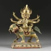 BEDEUTENDE UND SEHR FEINE FIGUR DES DAMCHEN GARWA NAGPO (DAMCAN), Tibet, 18. Jh., Bronze, sehr fein ziseliert, feuervergoldet, partiell farbig gefasst. H. 26,5 cm. Erlös: 21.200,-€