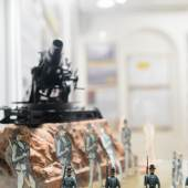 5 APRIL 1914 Soldaten c  Wolfgang Lackner Blick in die Ausstellung mit Sicht auf Soldaten aus Papier/dünnem Karton und Zinn; im Hintergrund: Modell eines österreichischen Mörsers Foto: Wolfgang Lackner