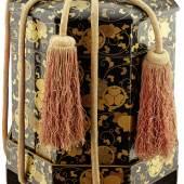 """943 / CHF 1400.– Grosses feines """"kaioke"""" Japan Edo-Periode. Achteckig mit leicht gewölbtem Deckel und Ständer aus Holz. Ein Behälter, von einem Paar, für das Aufbewahren der Muscheln für das """"kai-awase"""" Spiel. Auf schwarzem Lackgrund Dekor von Chrysanthemen und Tokugawa Wappen zwischen Ranken in Goldlack. Der Ständer mit Dekor von Muscheln und unten befestigten orangen Seidenkordeln. Leichte Gebrauchsspuren.  Höhe 49 cm"""