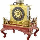 """954 / CHF 1800.– Feine """"Kopfkissen"""" Uhr Japan späte Edo-Periode. Sogenannte """"makura dokei"""". Das Gehäuse aus vergoldeter, mit Blumen gravierter Bronze, die seitlichen Türchen aus Glas, Auf rot lackiertem Holzsockel mit Metall-Balustrade. Der Uhrschlüssel in Schublädchen. Teil der Balustrade ergänzt. Zu revidieren.  Breite 14.1 cm Höhe 15.5 cm"""