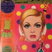 """Enchanted Books A blast from the past, this paper doll version of fashion icon Twiggy is delightful. Making this extra nice - it includes a separate free-standing cardboard die-cut of Twiggy wearing the """"Plastilon"""" dress - advertising the """"Twiggy Paper Doll Book plus a Mod Fashion that You Can Wear!"""