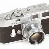 Leica M3 Chrom Doppelaufzug Nr. 700001 (1953)  Dies ist die erste Leica M3 aus der Serienproduktion mit Prototype Doppelhebel-Summicron 2/5cm Nr.922006. Die Firma Leitz reservierte 1953 für die neue M3 die Seriennummern ab 700000, tatsächlich wurde die Nummer 700000 erst 2 Jahre später in neuer technischer Ausführung als Präsentationskamera für Prof. Kruckenhauser vergeben. Deshalb ist 700001 die tatsächlich erste M3 (fertiggestellt September/Oktober 1953) und laut den Aufzeichnungen von Arthur Dauber aus der Entwicklungsabteilung von Leitz wurde die Kamera Willi Stein (Chefkonstrukteur von Leitz) zugeordnet. 1975 wurde sie von Theo Kisselbach (siehe 'Vidom 87' Seite 16) erworben, seit 1984 ist sie im Besitz von seinem Sohn Günter Kisselbach. Willi Stein hatte die Kamera mit einem späteren Gehäuse mit grauem Leder versehen, nun wurde von Ottmar Michaely eine Orginalschale mit 4 Schrauben und korrektem Leder eingebaut. Das Prototyp Summicron Nr. 922006 ist im 'Vidom 92 Seite 9 beschrieben. Diese für die Leitz Geschichte so wichtige Kamera ist in perfektem technischen und optischen Zustand!  Startpreis: 80.000 EUR Schätzpreis: 160.000-200.000 EUR Verkauft: 900.000 Euro