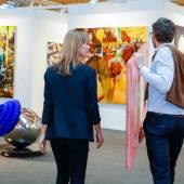 """Ein Paar erwirbt Kunst direkt beim Galeristen auf der art Karlsruhe, im Hintergrund Franziska Maderthaner, """"Dead Hand"""", 2017 Foto: KMK/Jürgen Rösner"""