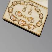 Außerordentliches antikes Muschelgemmencollier mit Ohrgehängen und Schließe. Muschelgemmenschnitzerei mit Darstellung von Helios im Sonnenwagen, spielenden Putten und Engelsköpfen. Originale Fassung, vermutlich 18 ct. GG. Anf. 19. Jh. Im Etui