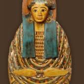 Mumienbrett der Dame Nes-Mut, deren vollständiges Sargensemble ausgestellt ist. Auf der Brust und um die Schultern ist ein farbenfroher Blumenschmuck dargestellt. Dritte Zwischenzeit, um 900 v. Chr. Leihgabe aus dem Ethnographischen Museum Neuchâtel.
