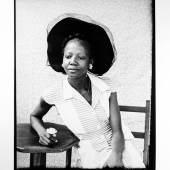 Seydou Keita, Sans titre (femme au chapeau, à la fleur et au guéridon), 60 x 90 cm, Tirage au Bromure dárgent. Signé et daté. Estimate: € 20 000 - 30 000 (c) ARTCURIAL