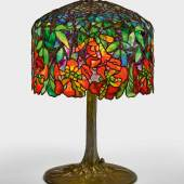 "Lot 327 Property from The Shedlarz Collection Tiffany Studios An Important ""Trumpet Creeper"" Table Lamp with a ""Tree"" base underside of shade mounting post impressed 28277 and 11 mounting pin on shade impressed 11 top of base column impressed 11 base plate impressed TIFFANY STUDIOS/NEW YORK/28277 and 11 underside of perimeter base cushion impressed 11 leaded glass, patinated bronze 27 1/4 in. (69.2 cm) high 18 1/2 in. (47 cm) diameter of shade circa 1903 Estimate $800,000/1.2million Sold for $2,"