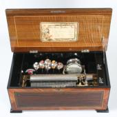 Musikdose «Tambour, Timbres en vue». Jules Cuendet, L'Auberson um 1895. 8 Musikstücke; Stimmkamm mit 66 Tönen; 6 Glocken und Trommel mit 8 Schlegeln. Das «Columbia»-Musikwerk wurde komplett von der Fa. Paillard & Cie., Ste-Croix, zugeliefert. 70 x 36 x 26 (56) cm (L. x T. x H., ( ) H. mit geöffnetem Deckel).  (c) Museum für Musikautomaten Seewen SO