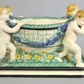 """PRUNKSCHALE """"Korb mit Putten"""" die 4 kleinen Figuren tragen einen Korb mit Blumengirlande über die blühende Wiese.farbig bemalt auf hellem Scherben, Entwurf Wilhelm Süs, Karlsruher Majolika (Pressmarke) um 1910, 24x34x19cm.  Mindestpreis:350 EUR"""