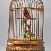GOLDENER VOGELKÄFIG mit 2 Vögeln mit bunten Federn auf einem Ast sitzend, der Vogel mit rot-braunem Gefieder bewegt den Schnabel zum Pfeifen, im Sockel eingebaut eine Spieluhr, die zu den Bewegungen des Vogels spielt, vergoldeter Metallkäfig mit Stucksockel (leicht beschädigt) 19. Jh. H 50cm, *Spieluhr wird mit Schlüssel aufgezogen und läuft*. Mindestpreis:180 EUR