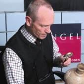 Auktionator Wolfgang Engel Begutachtung eines Kunstwerkes