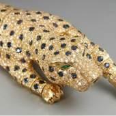 Prächtiges Panther- Armband/Brosche in Cartier-Art. 750 GG. 99,1 g. Einfuhrpunze Österreich ab 30.07.1925. Großes, halbplastisches, partiell beweglich gegliedertes Tier, besetzt mit ca. 1000 Brillanten (zus. 10,40 ct/ Weiß/Vsi), 152 Saphiren (zus. 12,10 ct) in Pavéfassung und 2 Smaragd-Augen (zus. 0,10 ct) Verschließbar durch Kastenschloß mit 2 Achtersicherungen an Tatze mit Schwanzende, sowie abnehmbarer, 2-nadliger Steg mit Haken- und Kugelhakenverschluß. 17,5 x 3 cm. ABB.B 19