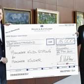Robert Ketterer, Auktionator und Inhaber von Ketterer Kunst (links) übergibt Christian Netzer, Vorstandsvorsitzender der Münchner Kindl-Stiftung (rechts) einen Scheck mit der bei der Versteigerung erlösten Summe von € 15.000