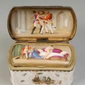 Seltene Tabatiere mit versteckten erotischen Motiven. Ungemarkt, Loosdrecht, um 1775-1780. Rechteckige Dose mit metallmontiertem Scharnierdeckel. Auf der Wandung in kleinen Kartuschen gemalte Militärszenen, goldstaffierte Reliefrocaillen und Streublümchen. Doppelbödiger Deckel, darauf im geschlossenen Zustand eine Watteauszenen-Malerei, im geöffneten Zustand 2 gemalte erotische Szenen. Gold berieben. H 5,5 cm, B 5,2 cm, L 9,1 cm. Zur Form vgl. Beaucamp-Markowsky, Barbara, Porzellandosen des 18. Jahrhunderts, Nr. 536. ABB.B 184