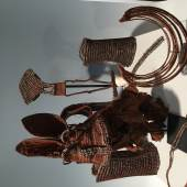 Louis Nierijnck  The body adornment of the Himba people,  includes a pair of anklets, also worn as a protection against snake-bites. Ekori headdress, worn after marriage. Also various neck ornaments.