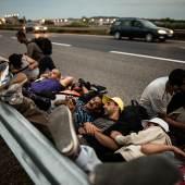 stván Bielik Auf dem Fußmarsch von Budapest Richtung österreichische Grenze rasten syrische Flüchtlinge am Rand der Autobahn M1, Ungarn 2015 © István Bielik